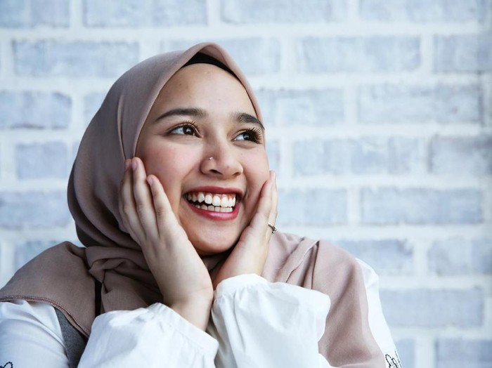 A women touch her face and smile with excitement