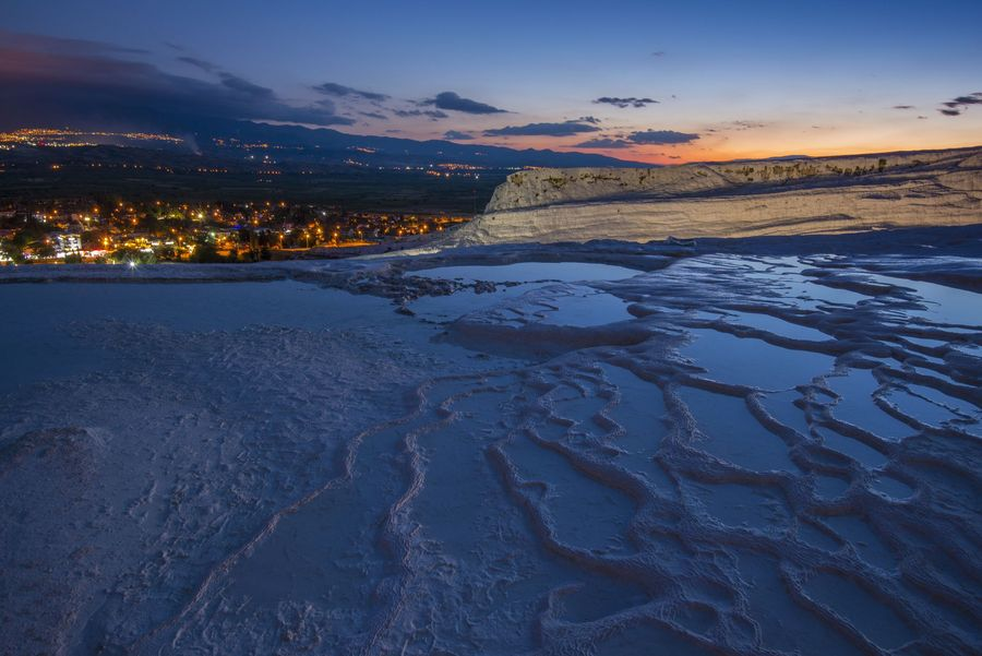 Illuminated Pamukkale terraces against sunset sky background. Denizli city lights in the middle of composition.