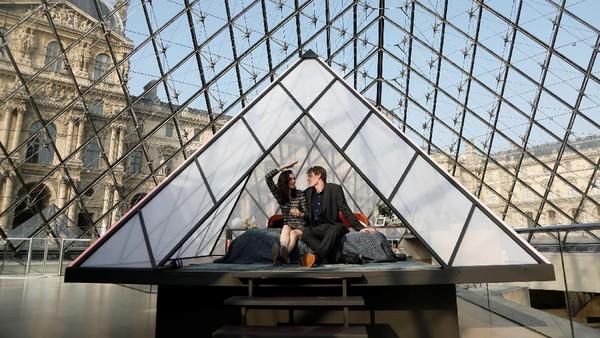 Kencan romantis ini ditutup dengan menginap semalam di piramida kaca Louvre yang sudah disulap seperti kamar hotel. (Reuters)