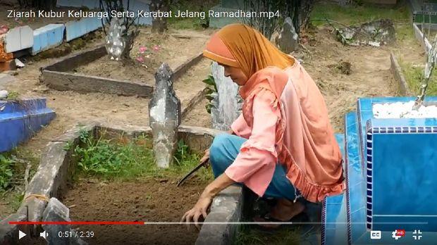 Ani terlihat membersihkan makam anaknya.