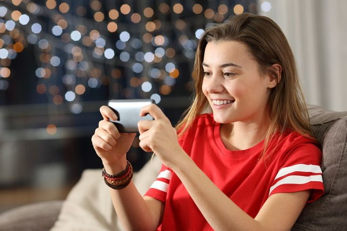 Teen watching media in a smart phone in the night sitting on a couch in the living room at home
