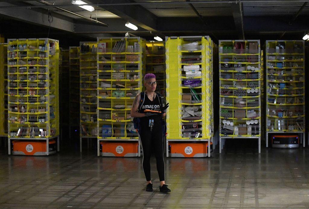 Amazon juga mengoperasikan belasan ribu robot di gudangnya untuk mempermudah perpindahan barang. Terlihat robot itu berada di bawah semacam kontainer barang dan bisa bergerak sesuai program. Foto: Reuters