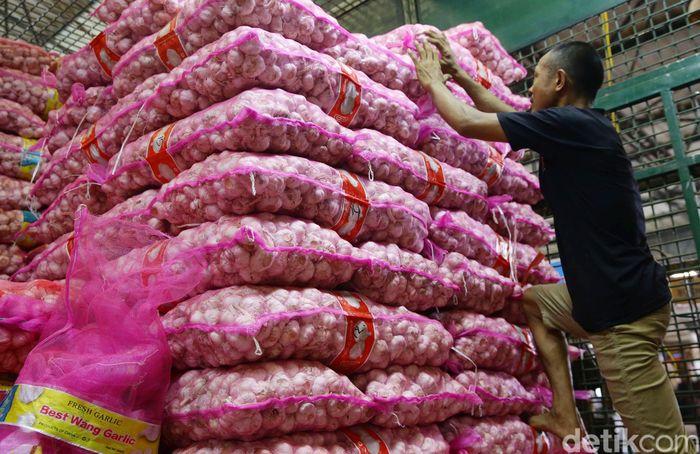 Pekerja menata tumpukan karung bawang putih di Pasar Induk Kramat Jati, Jakarta, Selasa (7/6/2019).