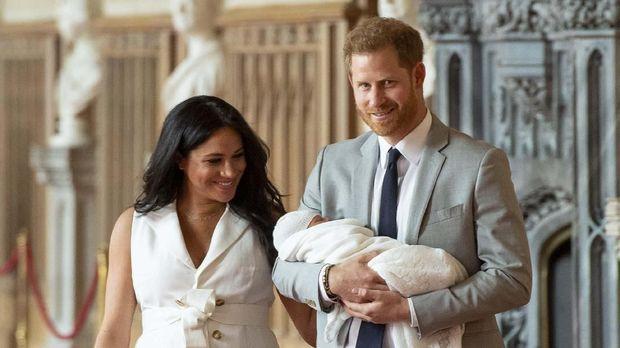 Pangeran Harry menggendong putranya saat menunjukkan ke publik untuk pertama kalinya.