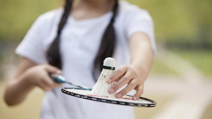 Chinese girl holding badminton racket and shuttlecock