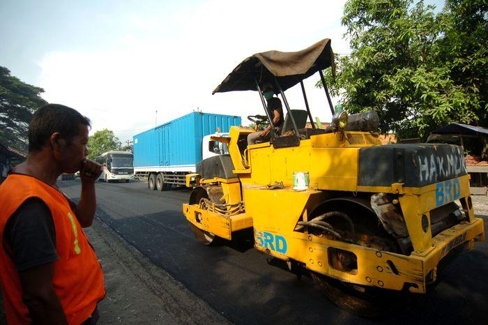 Pekerja menyelesaikan perbaikan jalan di jalur Selatan Tegal-Purwokerto, Desa Prupuk, Kabupaten Tegal, Jawa Tengah.
