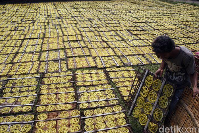 Pekerja tengah menjemur kerupuk mie mentah di industri kecil rumahan, Karadenan, Kabupaten Bogor, Jawa Barat. ANTARA FOTO/Yulius Satria Wijaya.