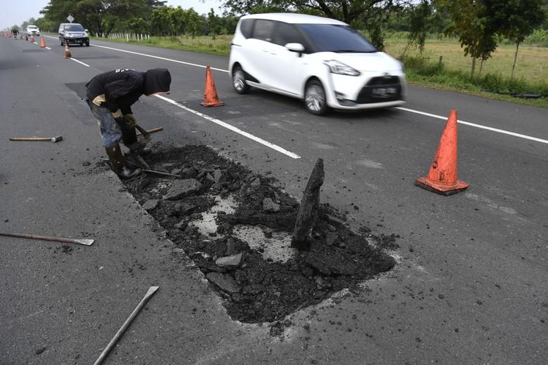 Pekerja menyelesaikan perbaikan jalan di Tol Brebes-Pejagan, Jawa Tengah, Minggu (12/5/19). Perbaikan dan pemeliharaan sejumlah ruas tol dilakukan jelang mudik Lebaran 2019. ANTARA FOTO/Puspa Perwitasari/ama.