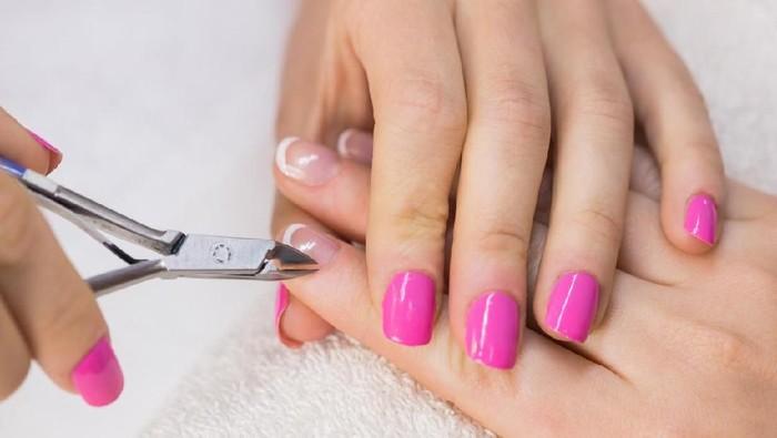 Nail technician clipping customers nails at the nail salon