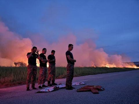 Para petugas pemadam kebakaran Malaysia juga salat berjamaah di jalanan usai menjalankan tugasnya