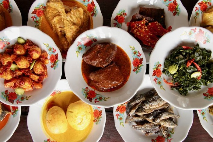 Assortment of Minangkabau dishes served on the table in hidang style; means serving the eaterys menu on the table. The dishes are plated on small ceramic plates and stacked as to save some spaces on the table.