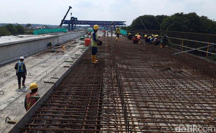 Sejumlah pekerja tampak merangkai besi untuk beton cor.