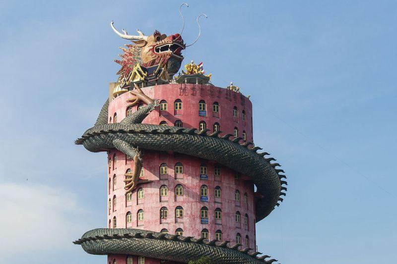 Ini adalah Wat Samphran, vihara berwarna merah muda yang dililit oleh naga raksasa. Ini menjadi ciri khas dari vihara Thailand. (iStock)