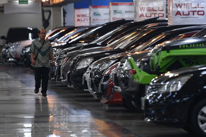 Seorang warga melintas diantara deretan mobil bekas yang dijual di Bursa Mobil bekas WTC Mangga Dua, Jakarta Utara, Jumat (17/5/2019).