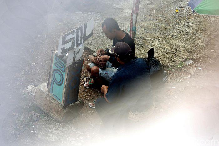 Seorang tukang sol saat melayani warga yang hendak memperbaiki sepatu.