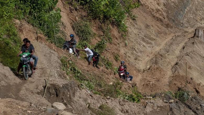 Aksi Nekat Warga Lewati Tebing Akibat Jalan Putus Diterjang Banjir