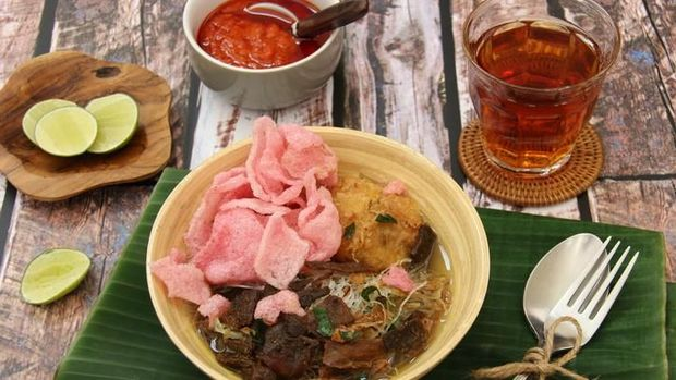 Soto Padang, the traditional beef jerky soup from Padang, West Sumatra. Crispy beef jerky with potato patty and glass noodles served in clear, spicy beef broth. Accompanied with pink tapioca crackers. The soup is plated in a ceramic bowl and placed on a plate lined with banana leaf. A set of rustic cutlery is placed on the plate.
