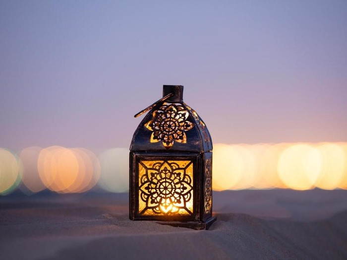 Traditional ornamental arabic lantern with a burning candle in desert after sunset during blue hour. Festivel greeting card for Ramadan Kareem and Ramadan Mubarak. Dubai, UAE.