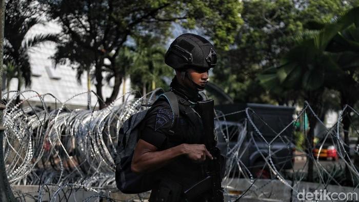 Sejumlah personil Kepolisian Brimob mempersiapkan pengamanan di depan KPU,  Jakarta,  Selasa (21/5). Pasca pengumuman rekapitulasi Pemilu 2019 yang dilakukan dini hari tadi oleh KPU, personel gabungan kepolisian semakin memperketat pengamanan Gedung KPU untuk mengantisipasi aksi 21-22 Mei di kawasan tersebut.