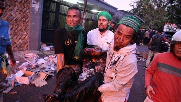 Sejumlah warga menggotong rekannya yang terluka dalam kerusuhan di tengah Jalan KS. Tubun, Petamburan, Jakarta Pusat, Rabu (22/5).