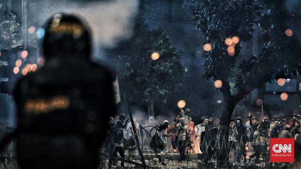 Polisi menggunakan gas air mata untuk menghalau massa rusuh.