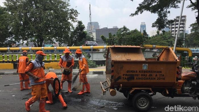 Pasukan oranye atau Petugas Prasarana dan Sarana Umum (PPSU) membersihkan sampah-sampah dan abu sisa bakar-bakaran demo di Jatibaru Tanah Abang, Jakarta.