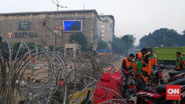 Petugas PPSU membersihkan sisa-sisa kerusuhan di Jl Thamrin depan gedung Bawaslu, Kamis (23/5) pagi.