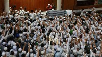 Para jemaah dan santri menyambut kedatangan jenazah Arifin Ilham.