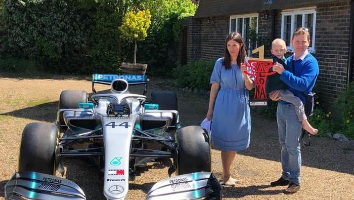 Seorang bocah pengidap kanker mendapat hadiah dari Lewis Hamilton berupa mobil F1. Foto: Foto: Twitter/@F1