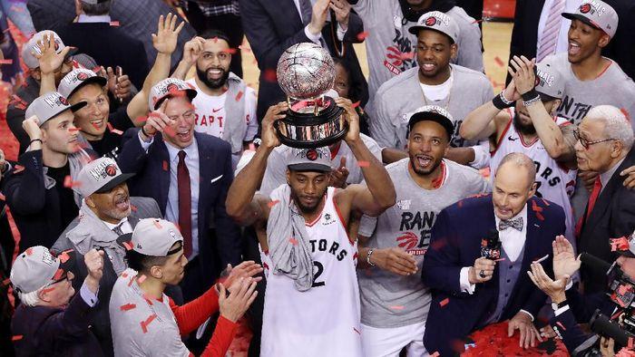 Pemain Toronto Raptors Kawhi Leonard mengangkat trofi juara NBA Wilayah Timur. Raptors pun maju ke Final NBA secara nasional untuk pertama kalinya. (Foto: Claus Andersen/Getty Images)