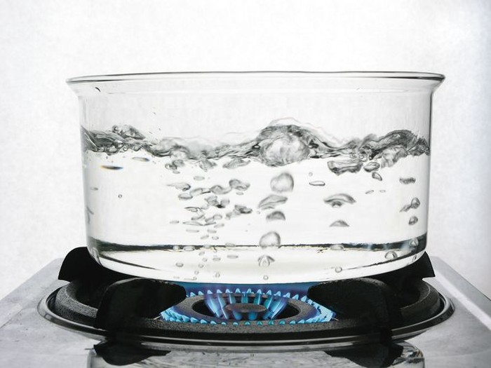 Water boiling in a clear glass pot.