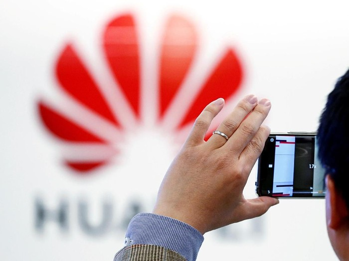 Ilustrasi seseorang memotret logo Huawei. Foto: Reuters