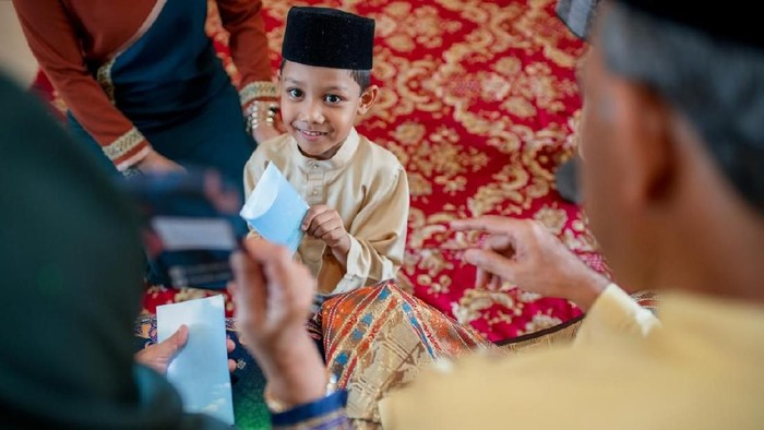 Young boy being presented with a gift of money from his grandparents as part of the Islamic celebration of Hari Raya Aidilfitri (Eid al-Fitr). Kuala Lumpur, Malaysia. May 2018