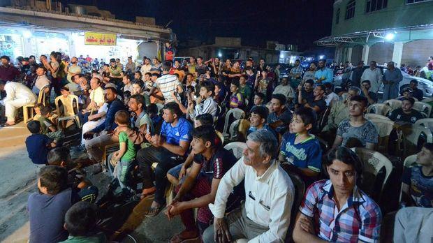 Masyarakat menyaksikan Abdel Wahed mendongeng di Mosul usai menjalani ibadah tarawih.