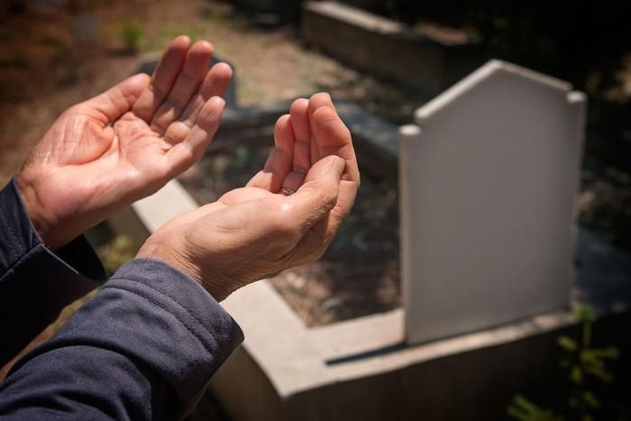 elderly muslim woman hands praying near the grave