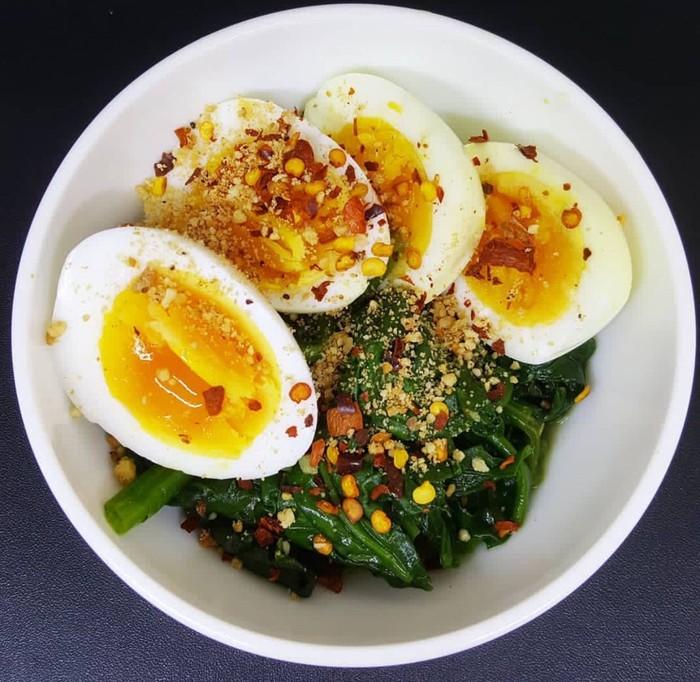 Telur rebus 7 menit ini dipadukan dengan bayam rebus, disantap hangat dengan taburan cabai kering dan bawang. Enaknya. Foto : Instagram @linatan92