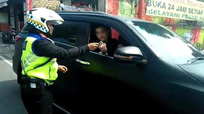 Pria pengendara Fortuner berpelat dinas Polri ditilang di kawasan Puncak. (Foto: Istimewa)