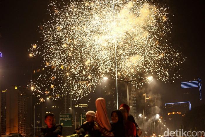 Sejumlah warga menyaksikan kembang api dan petasan di Jalan KH Wahid Hasyim, Jakarta. Pesta kembang api dan petasan ini menghiasi perayaan malam takbiran Idul Fitri.