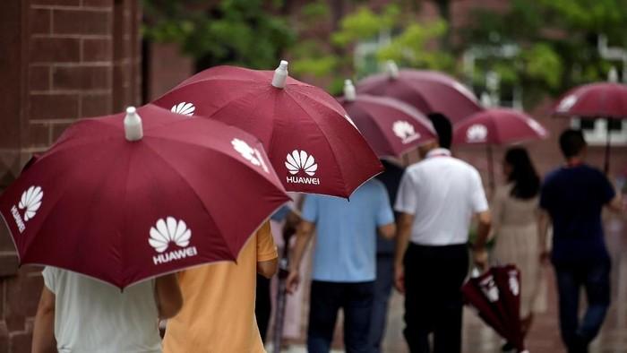 Karyawan Huawei berpayung. Foto: Reuters