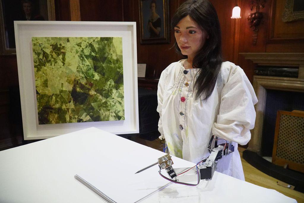 Ai-Da berpose dengan pensil di tangan mekaniknya, hendak membuat sketsa. (Foto: Matthew Stock/Reuters)