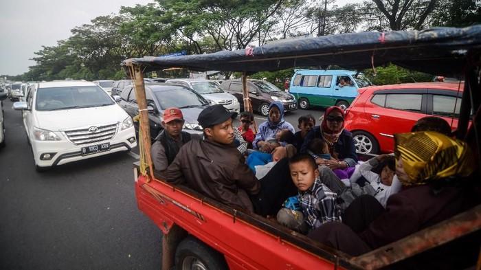 Sebuah keluarga dengan menggunakan mobil bak terbuka yang menuju gerbang tol Pasteur terjebak kemacetan di turunan jalan layang Pasupati, Bandung, Jawa Barat, Sabtu (8/6/2019). Petugas Jasa Marga Pasteur mencatat, pada Sabtu (8/6/2019) kendaraan yang memasuki gerbang tol Pasteur menuju Jakarta hingga pukul 13.30 sebanyak 12.139 kendaraan. ANTARA FOTO/Raisan Al Farisi/foc.