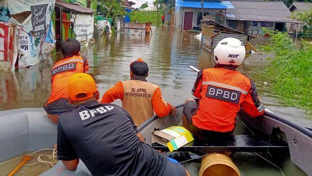 Personel BPBD menyisir kawasan permukiman dengan perahu karet.