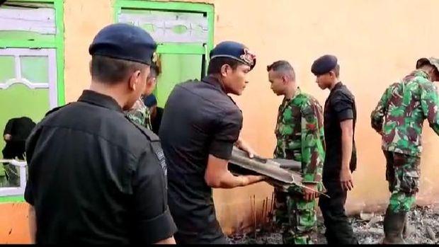 Personel TNI dan Polri saling bantu mengangkat puing.