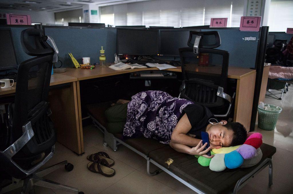 Seorang pegawai Huawei menatap smartphonenya sambil tiduran di kubikel, di kantor Huawei di Shenzen. Foto: Getty Images