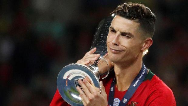 Cristiano Ronaldo memanggul trofi UEFA Nations League. (