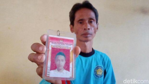 Sang ayah menunjukkan foto Amrih semasa hidup.