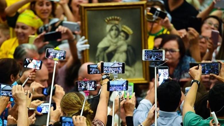 Ilustrasi turis yang memenuhi destinasi dengan tongsis (Vincenzo Pinto/AFP/Getty Images)