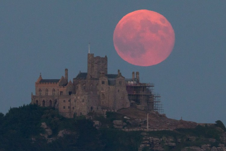 MARAZION, ENGLAND - JUNE 28:  A full moon rises behind St Michaels Mount in Marazion near Penzance on June 28, 2018 in Cornwall, England. Tonights strawberry moon, a name given to the full moon in June by Native Americans because it coincides with strawberry picking season, comes as parts of the UK continue to experience heatwave weather and record breaking temperatures. (Photo by Matt Cardy/Getty Images)