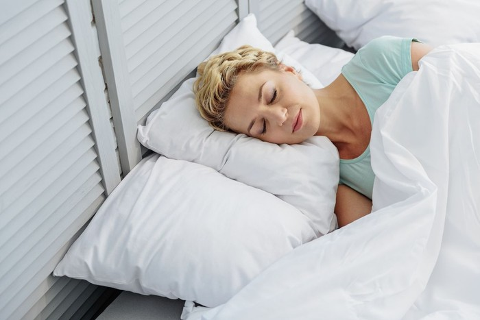 Calm middle-aged woman is sleeping on bed with pleasure