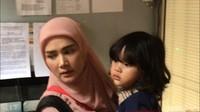 Mulan sesekali menutupi wajah anaknya itu dari sorot kamera wartawan.Hanif Hawari/detikHOT